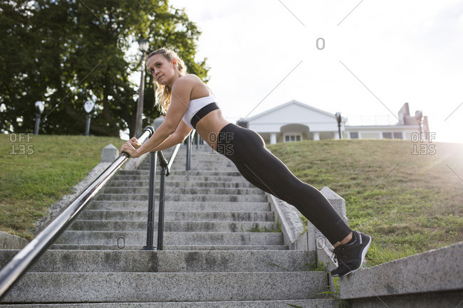 Young Adult Woman in Fitness Attire in Plank Position on Stone Stairs and Railing