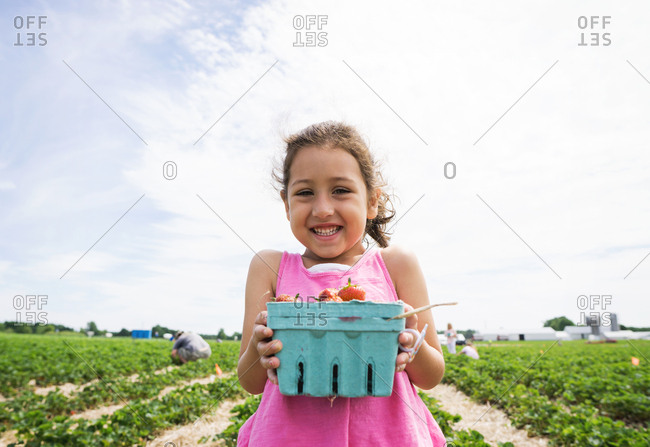 Smiling girl holding basket of fresh picked strawberries