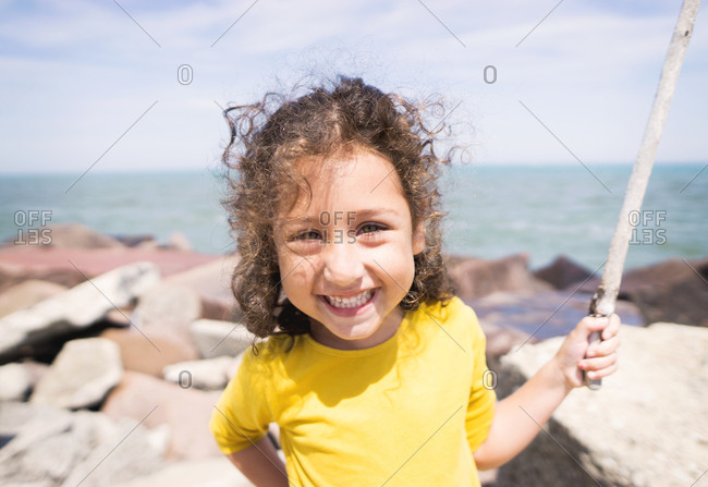 Close-up of young girl smiling and holding a large stick