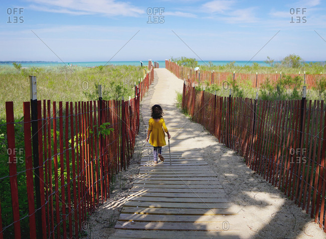 Young girl walking down boardwalk path to lake