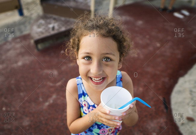 Smiling girl holding an iced drink in the summer