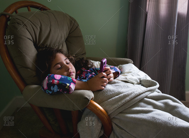 Young girl relaxing in a chair and playing on her phone