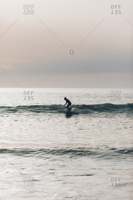 Surfer catching a wave in a muted dusk