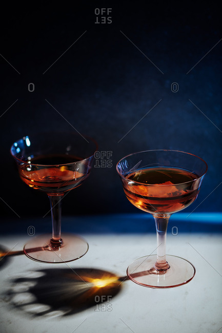 Classic Manhattan of whiskey, sweet vermouth and bitters served in two vintage depression era glasses served in a simple setting in hard light.