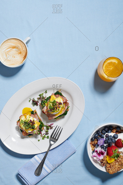 Overhead of eggs benedict with spinach, Canadian Bacon and a poached egg served with a latte and a mimosa, yogurt and granola bowl sits nearby with fruit including blueberries, strawberries.