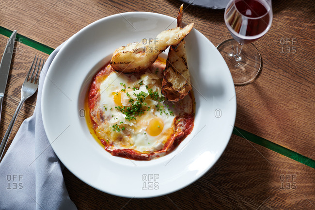 Eggs in Purgatory for brunch in morning light.  A dish of sunny side up eggs in a hearty tomato sauce with grilled sliced bread