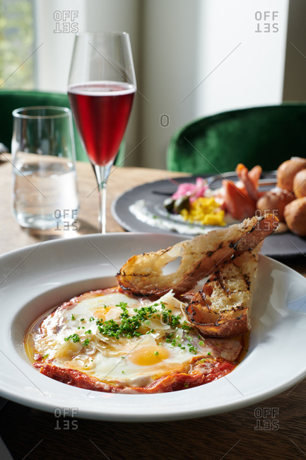 Eggs in Purgatory for brunch in morning light.  A dish of sunny side up eggs in a hearty tomato sauce with grilled sliced bread.  In the background a bagels and lox flavor remained by deconstructing the flavors of cream, dough in the form of hush puppies and chunks of smoked trout.  A sparkling red wine is served alongside.
