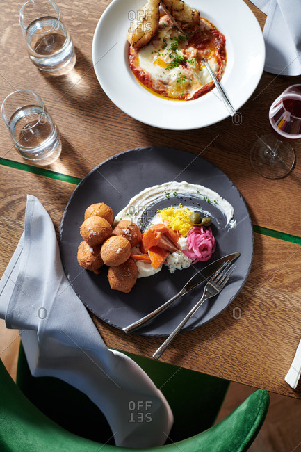 A smoked trout brunch dish with the flavors of bagels and lox reimagined and deconstructed, including hush puppies, cream cheese, smoked trout and pickled red onions.