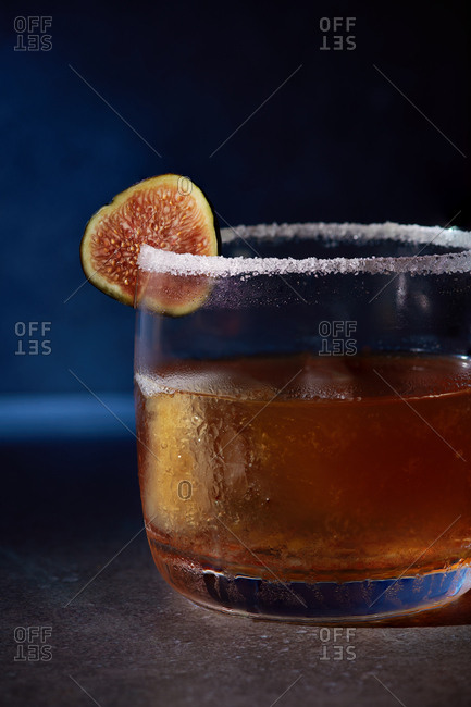 Cinnamon Fig Sidecar consisting of sour, cinnamon, orange curacao cognac, served in a rocks tumbler glass with a sugar rim and garnished with a black fig.