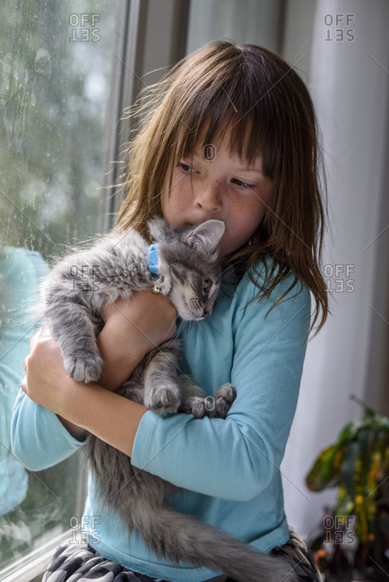 Young girl cuddling with baby kitten