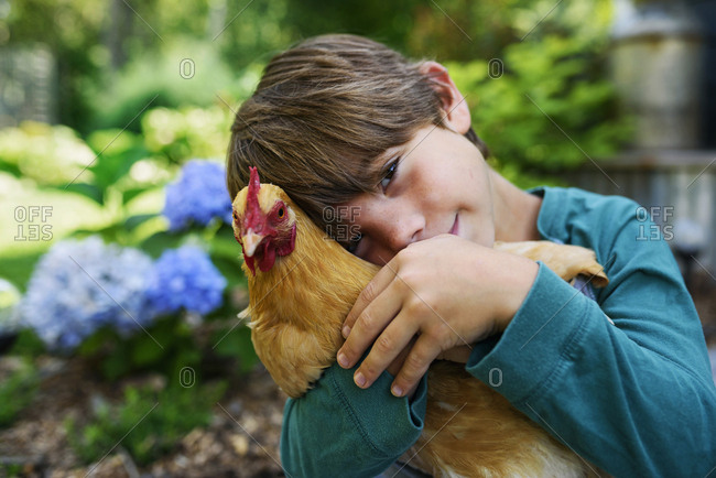 Young boy cuddling a chicken