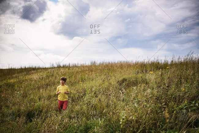 Young boy playing in a prairie with storm clouds