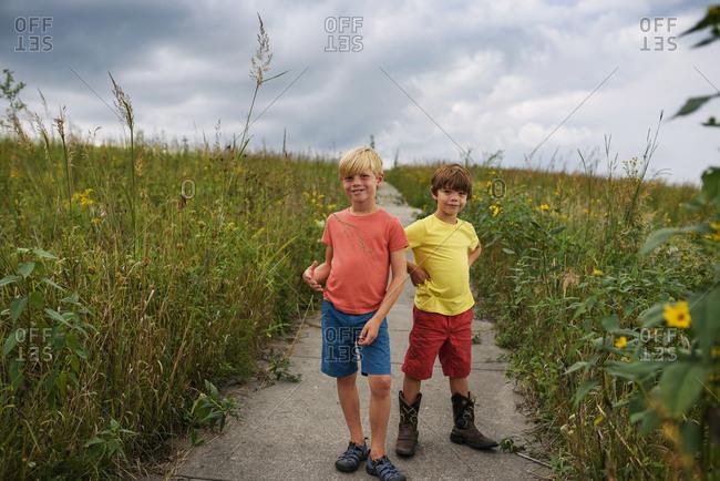 Two boys walking on nature prairie trail