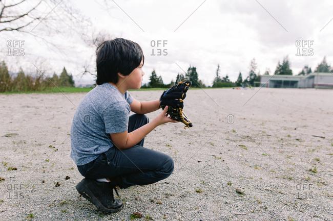 Boy with catcher's mitt playing baseball game