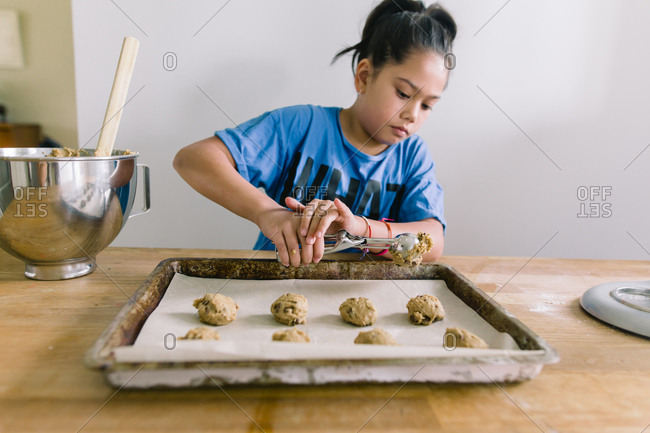 Girl scooping cookie dough onto sheet pan in kitchen