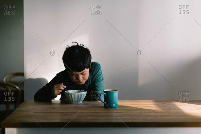 Boy sitting at table eating a bowl of cereal