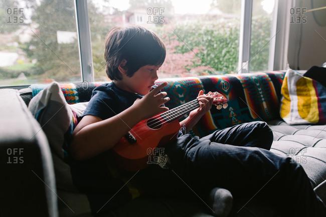 Boy sitting on couch strumming ukulele