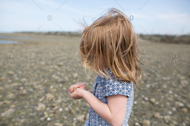 Little girl on rocky beach cupping hands together