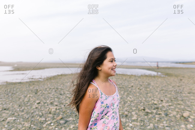 Smiling mixed race tween girl standing on rocky beach