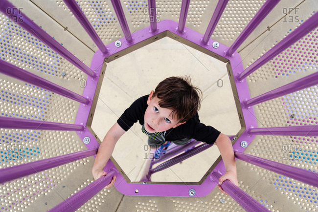 Overhead view of young boy climbing up ladder at playground