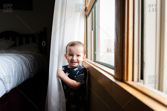 Toddler boy standing in curtains