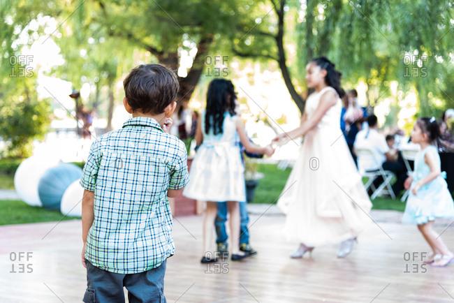 Toddler boy walking toward dance floor at outdoor wedding