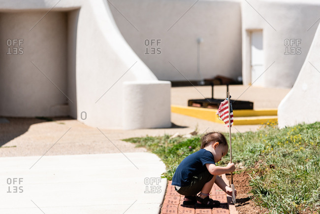 Toddler boy putting American flag in the ground