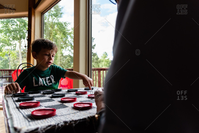Young boy playing checkers game with his grandfather
