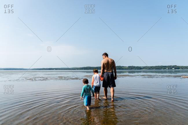 Two boys with dad swimming at beach
