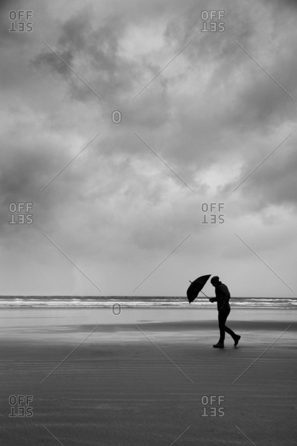 Man walking on Cox Beach in rain storm, Tofino, Vancouver island, British Columbia, Canada