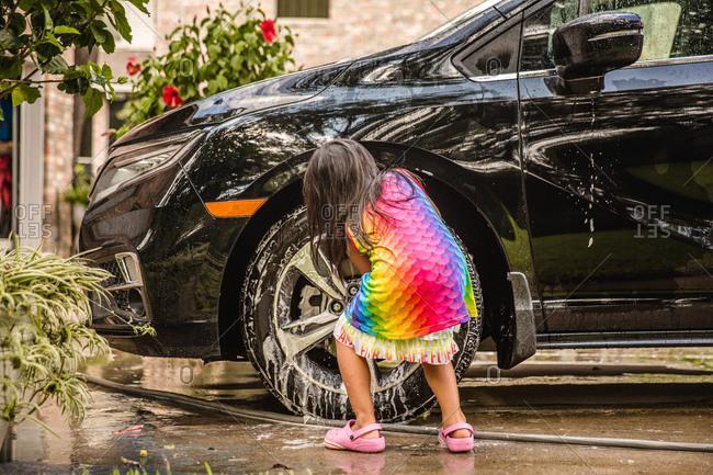 Little girl washing car tire