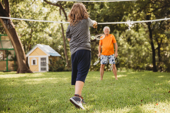 Boy playing badminton with his grandfather