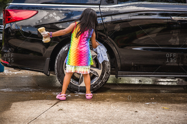 Rear view of little girl washing car tire