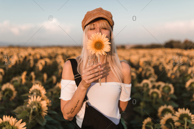 Front view of young blonde woman with beret and denim jumpsuit holding a sunflower in the middle of countryside in a sunset of summer