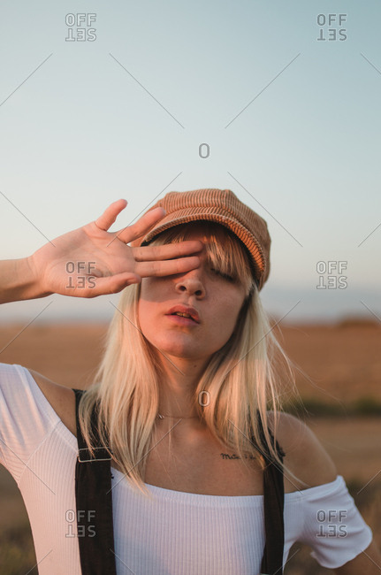 Portrait of young blonde woman with beret covering her eye in a sunset of afternoon