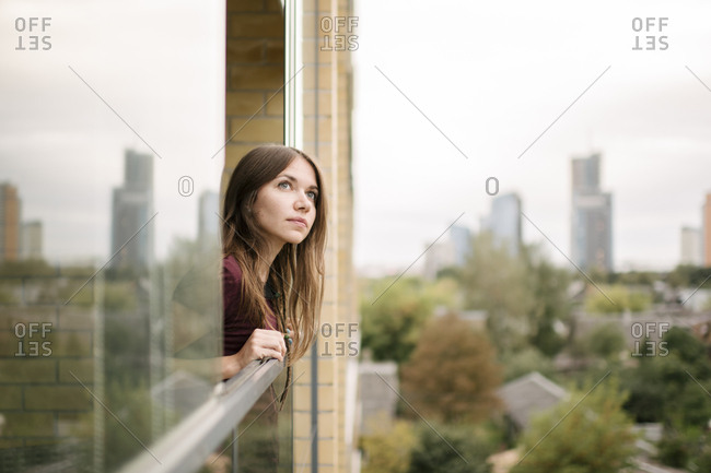 Girl looking from a window in the city