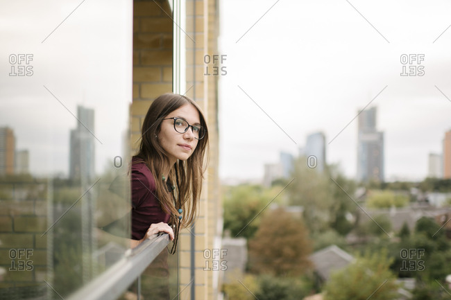 Girl looking from a window to the city