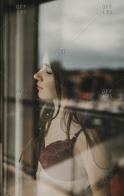 Young woman with eyes closed near to the window