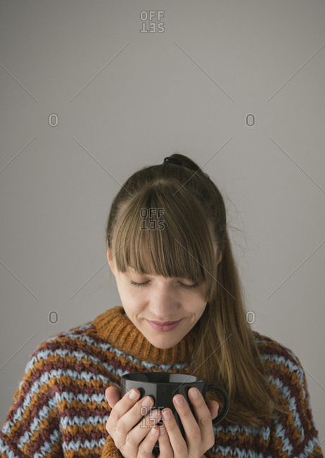 Young woman enjoying a cup of hot tea