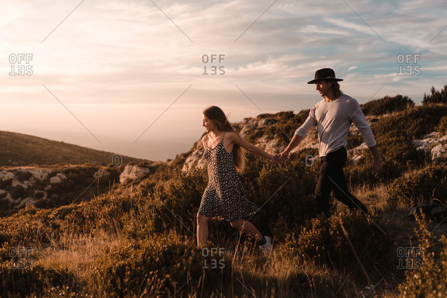 Side view of young vintage couple walks by a cliff in a sunset of summer mountains background