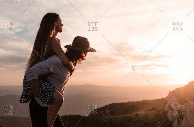 Rear view of young blond vintage man with black hat carrying his girlfriend piggyback in a cliff sunset and mountains background
