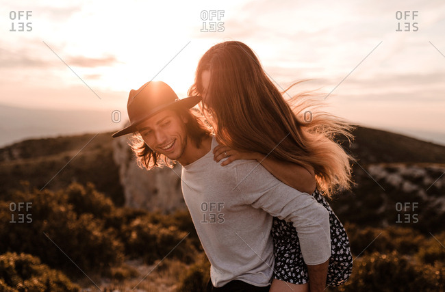 Young blond vintage man with black hat carrying his girlfriend piggyback in a cliff sunset and mountains background