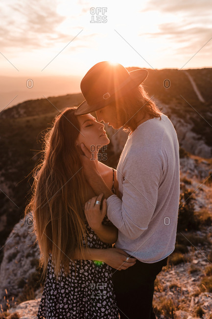 Side view of young vintage couple hugs and kissing in a cliff in a sunset mountains background