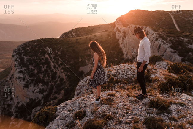 Side view of young couple walks by a cliff in a sunset