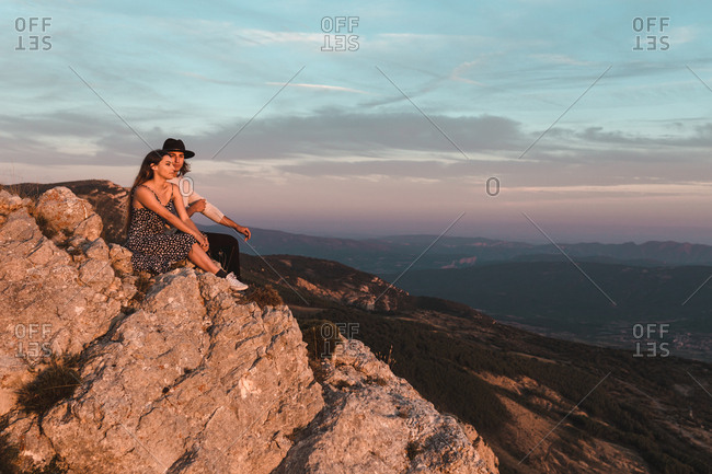 Side view of young vintage couple sitting in a cliff observing the sunset mountains background