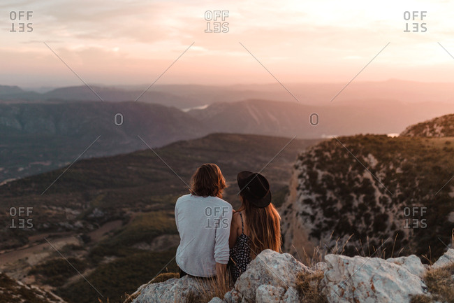 Rear view of vintage couple in a cliff observing the horizon in a sunset of summer mountains background