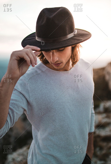 Portrait of young vintage blond man with black hat and long hair looking at camera in a cliff mountains background