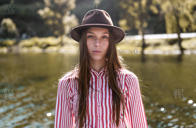 Portrait of young vintage woman looking at camera in a sunny day lake and mountains background