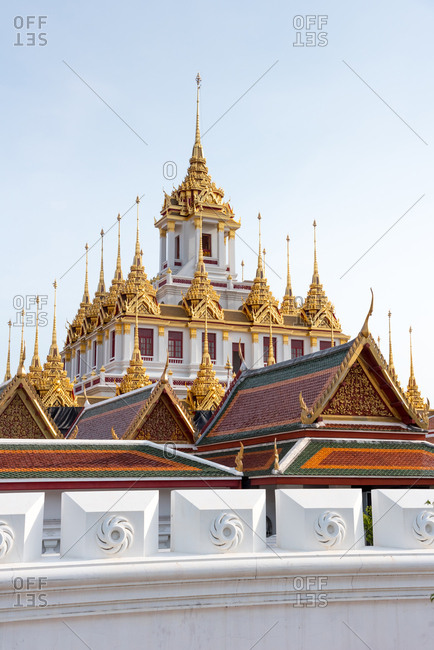 Views of Loha Prasat Temple in Bangkok on background of blue cloudless sky