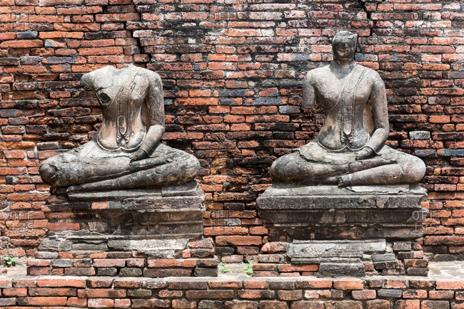 Ancient stone ruined statues of Buddha placed in front of brick wall in Ayutthaya